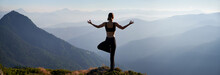 Back View Of Young Woman Performing Yoga Pose On Grassy Hill And Looking At Beautiful Mountains. Sporty Woman Standing On One Leg And Doing Gyan Mudra Hand Gesture While Practicing Yoga Outdoors.