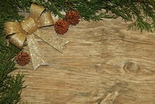 Cedar Branches And Gold Bow Winter Background