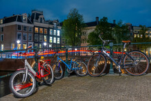 Bicycles On The Canal Embankment In Amsterdam At Night