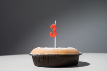 Small Cake With A Candle In The Shape Of The Number Three For Birthday.
