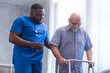canvas print picture - Caregiver is teaching old man to walk with walker. Professional nurse and patient in a nursing home. Assistance, rehabilitation and health.