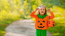 Blonde Girl Portrait In Pumpkin Costume With Pumpkin-shaped Basket For Sweets In Her Hand.