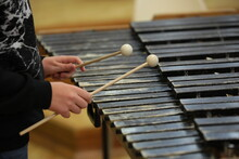 Person Playing Percussion Stick Hammer In Hand Hits Black Old Wooden Xylophone Keys Close-up Selective Focus.Background Image Of A Teenage Musician Learning To Play A Musical Instrument Marimba