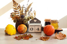 Calendar For November 4 : The Name Of The Month In English, The Numbers 0 And 4, A Bouquet Of Dried Flowers In A Basket, Pumpkins, Maple Leaves, Jam Jars On A Gray Table