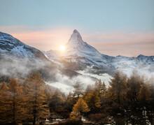 Sunset Behind Matterhorn And Foggy Forest.