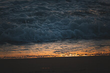 Foamy Waves Of The Ocean Washing The Sandy Beach At Golden Sunset
