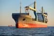 Leinwandbild Motiv Large crane ship (general cargo, 146 meters length) sailing in an open sea at sunset. Golden sunlight. Freight transportation, logistics, global communications, economy, industry, worldwide shipping