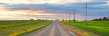 Rural Road Through The Field Under Dark Dramatic Rain Clouds. Electricity Line Close-up. Panoramic View. Transportation, Tourism, Driving, Freedom, Logistics Themes. Autumn Landscape. Seasons, Weather