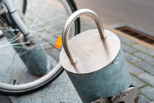 Close - Up On A Bicycle Rack Made Of Metal. Brick Pavement And Bicycle Wheel In The Background.