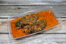 Traditional Climbing Perch Fish Boiled With Spicy Curry Paste And Coconut Milk Serving In The Plastic Tray. Famous  Thai Hot And Spicy Seafood Menu In Asia Restaurant.