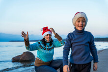 Happy Mom And Little Son Celebrate Christmas On The Beach In Christmas Hats, The Boy Laughs Merrily, Blurr
