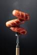 Leinwandbild Motiv Fork with grilled sausages on a black background.