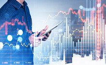 Businessman With Tablet In Hands, Graph Changes And Skyscrapers
