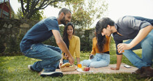 Shot Of Four Young South Asian Friends Sitting At A Picnic Blanket With Juices, Bananas, And Apples