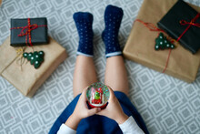 Little Girl Sitting On The Floor With Christmas Gifts Holding A Snowball. View From Above