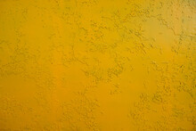 Abstract Background Of Dark Yellow Color With Splashes Of Green Paint. Decorative Plaster Or Wall Painted With Yellow Paint Over An Old Layer Of Green Paint. Old Rusty Metal Painted Yellow