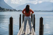 Mujer Observando La Naturaleza Desde Un Puente De Madera Con El Lago Y Las Montañas De Fondo.