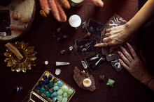 Top View Of A Tarot Card Spread. A Woman Points To One Of The Cards On Her Witch Altar With Several Semi-precious Stones On The Table