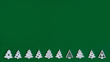 Small Figures Of Christmas Trees On A Green Background ,a Christmas Concept With A Place For Text