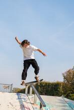 Jeune Garçon Adolescent Aux Cheveux Longs En Train De Sauter Et De Faire Des Acrobaties Avec Son Skate Board