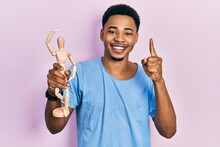 Young African American Man Holding Small Wooden Manikin Smiling With An Idea Or Question Pointing Finger With Happy Face, Number One