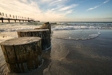 On The Coast Of The Baltic Sea On Zingst. The Pier And Groynes That Go Into The Water.