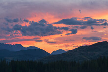 Dawn In The Mountains. Colorful Nature Scenery With Sunset Or Sunrise.  Atmospheric Landscape With Silhouettes Of Mountains With Trees On Background Of Orange Dawn Sky.