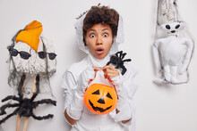 Horizontal Shot Of Scared Woman Stares Bugged Eyes Holds Carved Pumpkin And Spooky Spider Poses Against White Background With Creepy Creatures Around. Halloween Decor. Party And Celebration.