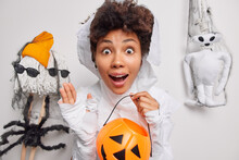 Surprised Scared Fearful Woman Holds Carved Pumpkin Cannot Believe Her Eyes Dressed In Ghost Costume Reacts On Horrible Scene Poses Against White Studio Background With Creepy Creatures Around