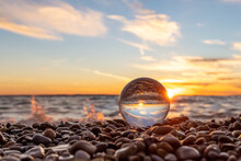 Clear Glass Ball Sitting In Colorful Rocks At Edge Of Lake Michigan Waves Crash Behind The Scene At Sunset.  The Sky Is Golden Sun And Blue Sky