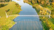 Top View Of A Long Pedestrian Bridge Over The Blue Odra River, Poland. Modern Suspension Bridge