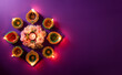 canvas print picture - Happy Diwali - Clay Diya lamps lit during Dipavali, Hindu festival of lights celebration. Colorful traditional oil lamp diya on purple background