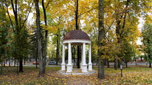 View Of An English-style Gazebo In A City Park In Autumn Against A Background Of Trees With Yellow Leaves