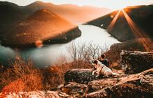 Man And His Dog Sitting On Rock Enjoying Amazing Autumn View Over Lake At Sunset