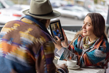 The Brown-haired Woman Is Holding A Tablet, She Shows Her Partner A Photo. Date Of A Couple In A Cafe For Tea. Cold Autumn Day.