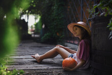 Little Girl In Hat Sitting And Holding Organic Pumpkin Outdoors At Farm.