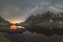 Tent In River Against Mount Under Starry Sky