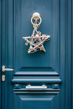 Front View Of A Star-shape Christmas Decoration Made Of Branches And Pine Cones, Hanging On A Blue Front Door With Moldings.