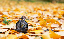 A Pocket Watch On A Dark Metal Chain Lies On Yellow Leaves. Autumn, Yellow-red Leaves In The Background