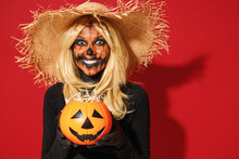 Young Smiling Woman With Halloween Makeup Mask Wears Straw Hat Black Scarecrow Costume Hold Pumpkin Jack-o-lantern Say Boo Isolated On Plain Red Background Studio. Celebration Holiday Party Concept