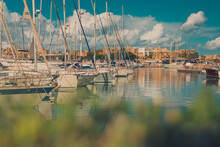 Beautiful View Of Marina In Valletta In Malta On A Sunny Day. Some Greenery In The Foreground And Fluffy Clouds On The Sky.