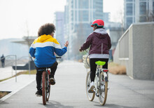 Teen Friends Riding Bicycles On Bike Path In City