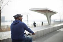 Man Riding Bicycle On Urban Boardwalk