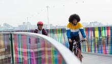 Teen Friends Riding Bicycles On Modern Footbridge In City, London, UK
