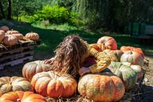 Blond Girl Sitting On Top Of Pile Of Gigantic Pumpkins