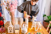 Boy Igniting Christmas Candle On Table