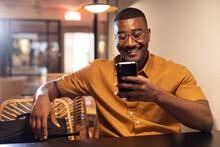 Smiling Black Man Using Smartphone In Cafe