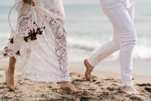 Anonymous Bride And Groom Running On The Beach