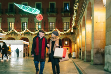 Woman With Father Walking On Square At Christmas Time