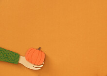 Pumpkin In Female Hands On Yellow Background
